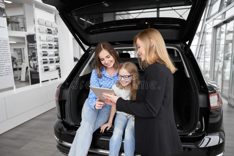 Female car dealer communicating with clients in showroom. Car dealer working with clients, instructing, showing information on gadjet. Mother and daughter stock photo