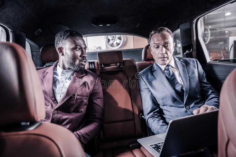 Two professional car dealers sitting in car with leather interior. Car dealers. Two professional car dealers sitting in car with leather interior with their royalty free stock photography