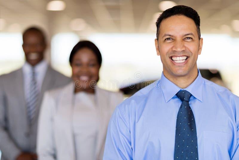 Car dealership principal staff. Cheerful car dealership principal with staff on background royalty free stock image