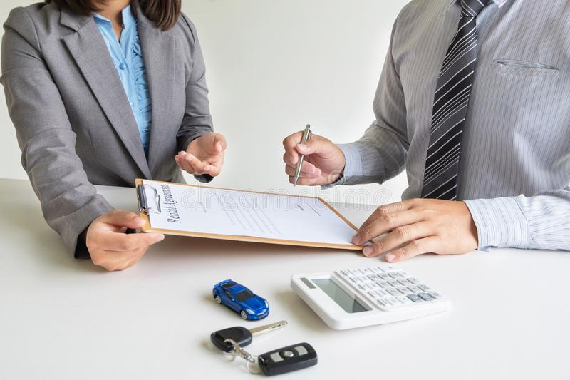 Car dealership provides advice about insurance details and car rental information and delivers the keys after signing the rental. Contract stock photo