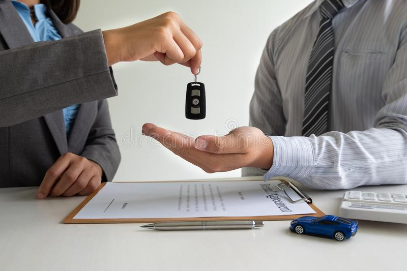 Car dealership provides advice about insurance details and car rental information and delivers the keys after signing the rental. Contract royalty free stock photos