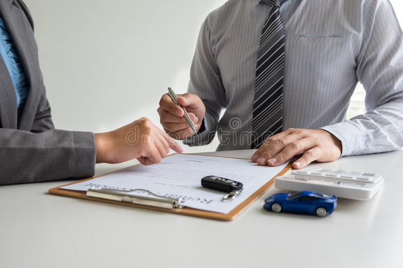 Car dealership provides advice about insurance details and car rental information and delivers the keys after signing the rental. Contract royalty free stock photography