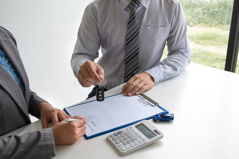 Car dealership provides advice about insurance details and car rental information and delivers the keys after signing the rental. Contract stock image