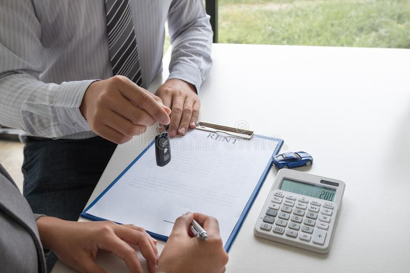 Car dealership provides advice about insurance details and car rental information and delivers the keys after signing the rental. Contract royalty free stock image