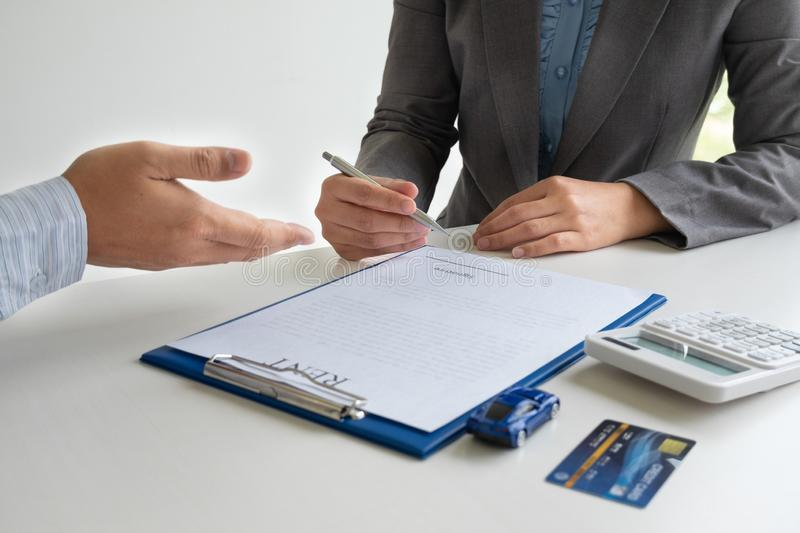 Car dealership provides advice about insurance details and car rental information and delivers the keys after signing the rental. Contract stock images
