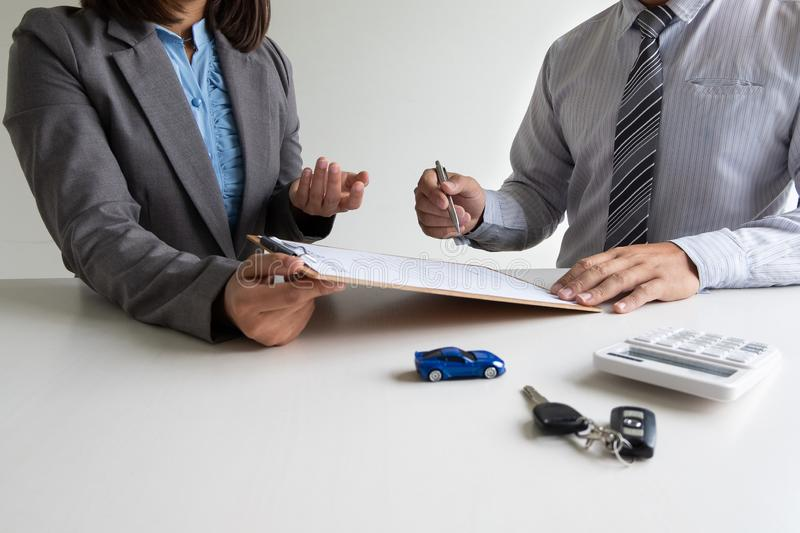 Car dealership provides advice about insurance details and car rental information and delivers the keys after signing the rental stock photo