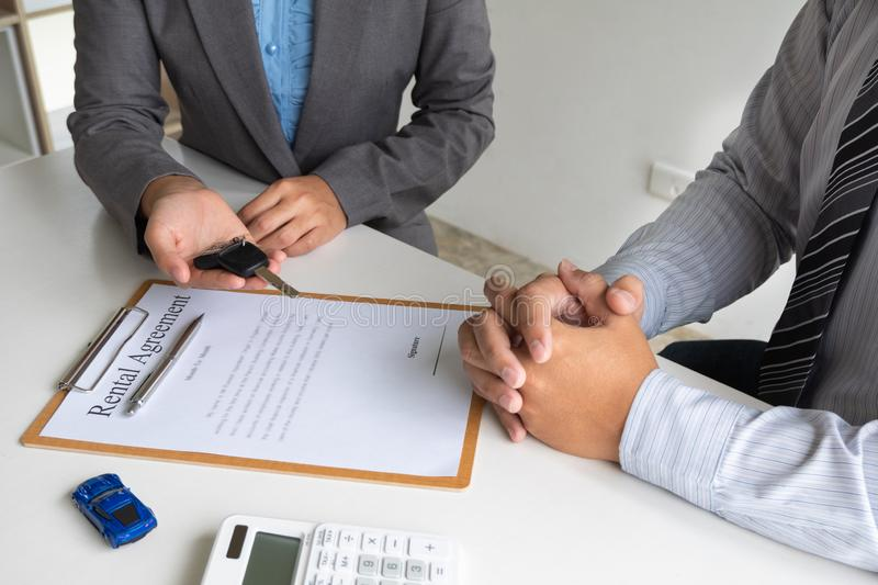 Car dealership provides advice about insurance details and car rental information and delivers the keys after signing the rental. Contract stock photography