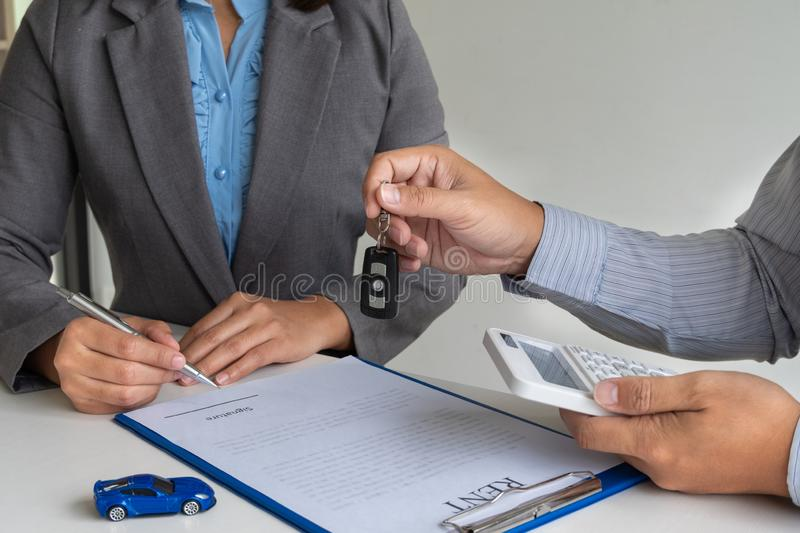 Car dealership provides advice about insurance details and car rental information and delivers the keys after signing the rental. Contract royalty free stock images