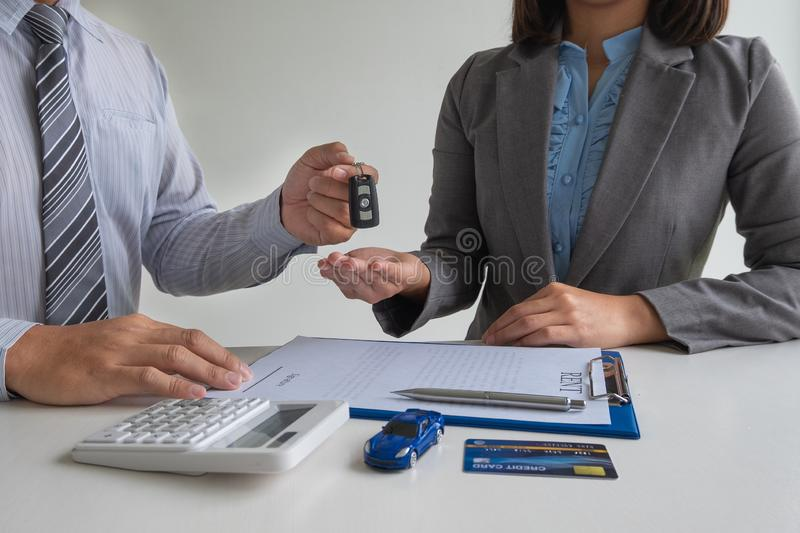 Car dealership provides advice about insurance details and car rental information and delivers the keys after signing the rental. Contract royalty free stock photo