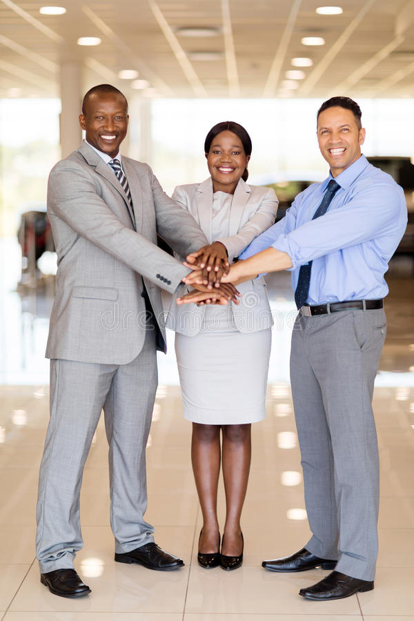 Car dealership staff hands together. Multiracial car dealership staff putting their hands together royalty free stock photos
