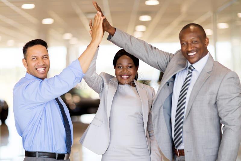 Car dealership staff high five. Successful car dealership staff giving high five in showroom stock photo