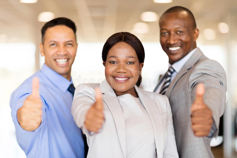 Car dealership staff thumbs up. Portrait of beautiful car dealership staff giving thumbs up royalty free stock image
