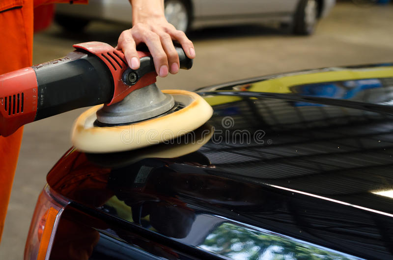 Car Detailing, Polished Black Car By Polishing Machine. Hands with daul action polisher. polishing on car surface. hand and foam pad in blur motion from stock images