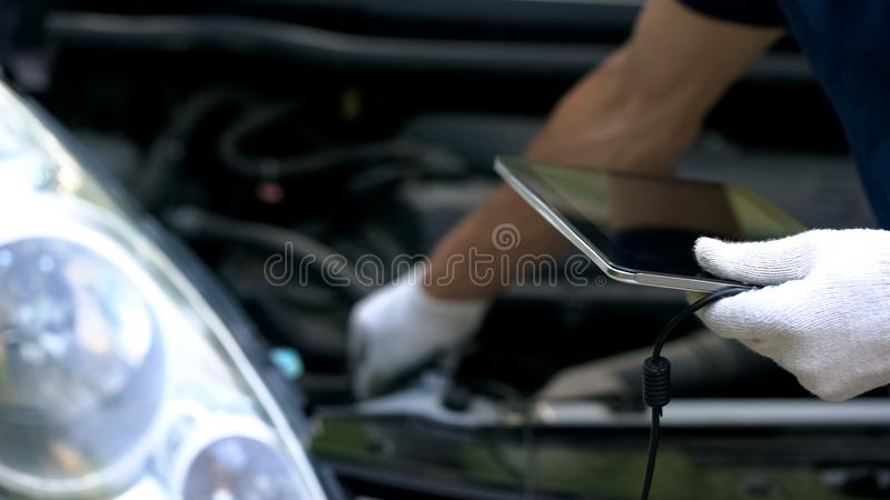 Car diagnostics with computer technologies, engineer uses tablet for auto repair royalty free stock photos