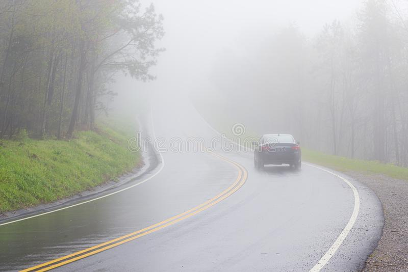 Car Disappears Into Dense Smoky Mountain Fog With Copy Space. Horizontal shot of a car disappearing into dense Smoky Mountain fog with copy space royalty free stock photography