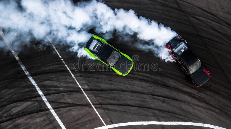 Car drift battle, Two car drifting battle on race track with smoke, Aerial view stock photo