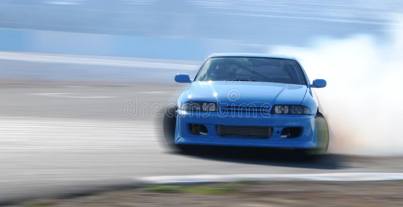 Car drifting on a race track. Blue car drifting on a race track with lots of smoke from wheels. Business concept of success royalty free stock photos