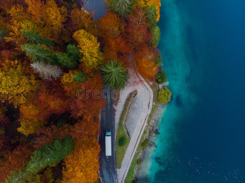 Car drive on road in autumn forest by lake, aerial view stock image