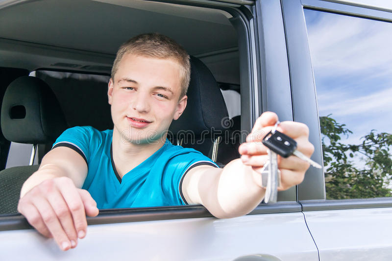 Car driver. Caucasian teen boy showing car key in the new car. Happy smiling young man behind the wheel. Travel and rental concept. Close up, outdoor royalty free stock images