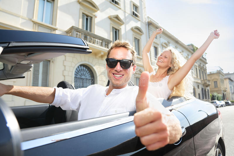 Car driver happy giving thumbs up - driving couple. Excited on road trip travel vacation. Male driver wearing sunglasses. Lifestyle with beautiful cheerful royalty free stock image