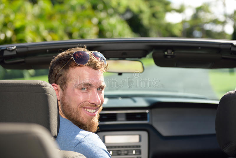 Car driver man driving convertible on a road trip. Portrait of a young Caucasian male adult looking at camera in his new or rental automobile happy to travel royalty free stock image