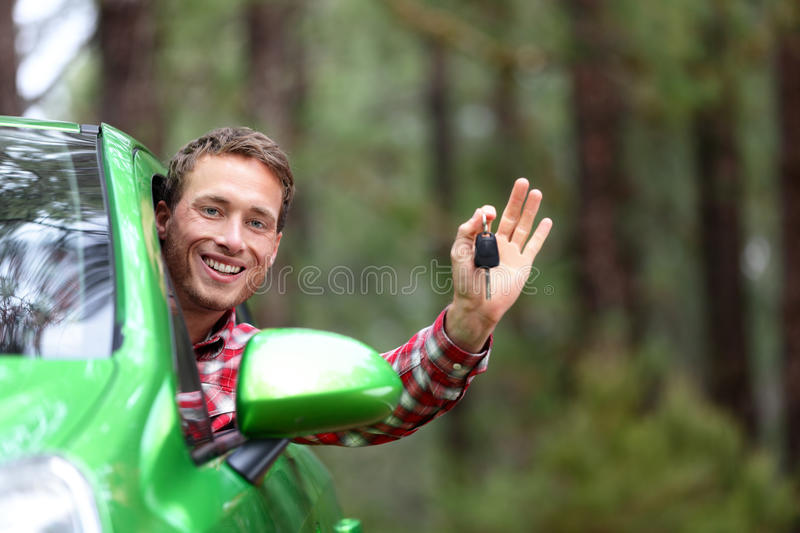 Car driver showing car keys happy. Car driver showing car keys and thumbs up happy. Young man holding car keys for new car. Rental cars or drivers licence stock images
