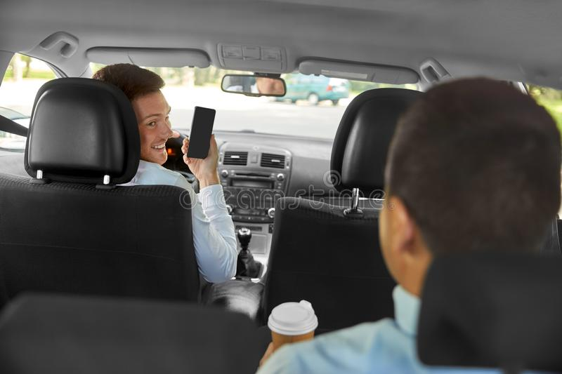 Car driver showing smartphone to male passenger. Transportation, taxi and technology concept - smiling car driver showing smartphone to male passenger stock photo