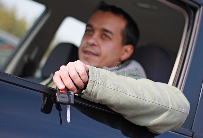Car driver sitting in his new car. Holding out keys royalty free stock image