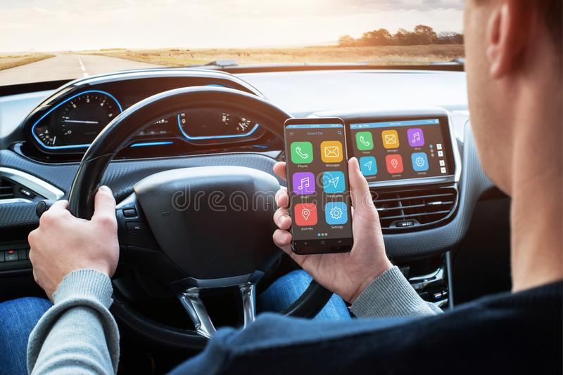 Car driver use smart phone with smart car app and use connection with car infotainment system stock photo