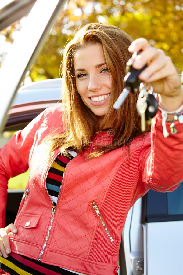 Car driver woman showing new car keys and car. Car driver woman smiling showing new car keys and car stock images