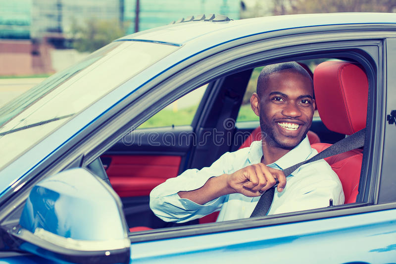 Car driver young man wearing safety belt driving new car. Car driver young man wearing safety belt driving new blue car in summer. Happy male looking at camera royalty free stock image
