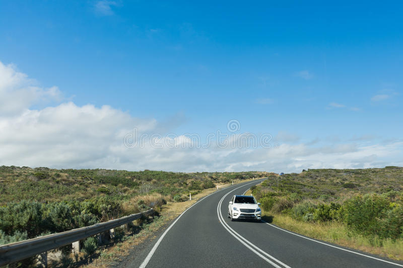 Car driving along curving coastal road on sunny day stock images