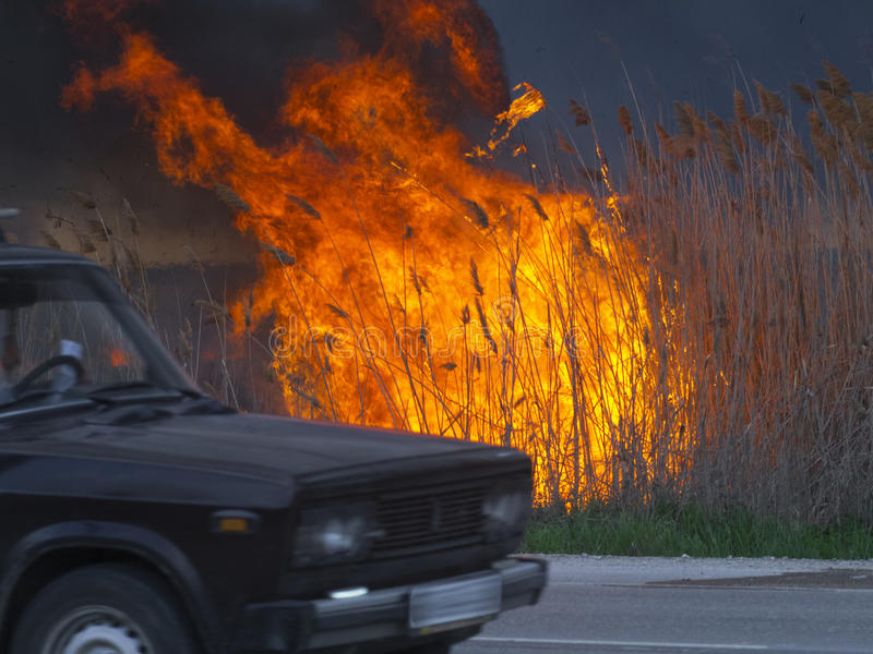 Car is driving along the road near the fire stock images