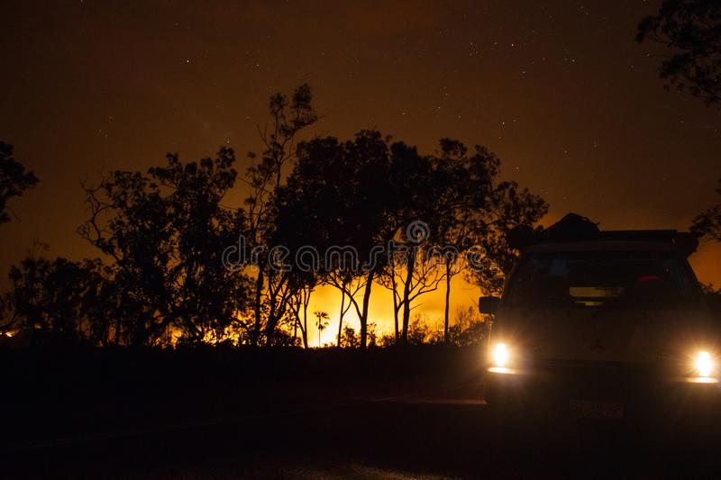 car driving away from a bushfire, forest is really bright because of the fire, litchfield national park, australia royalty free stock photo