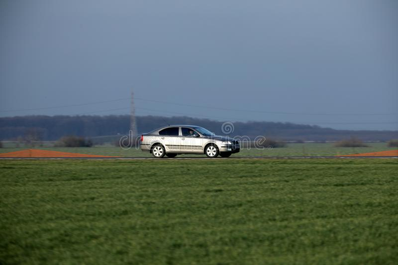 Car driving. A road in the middle of a green field stock photography