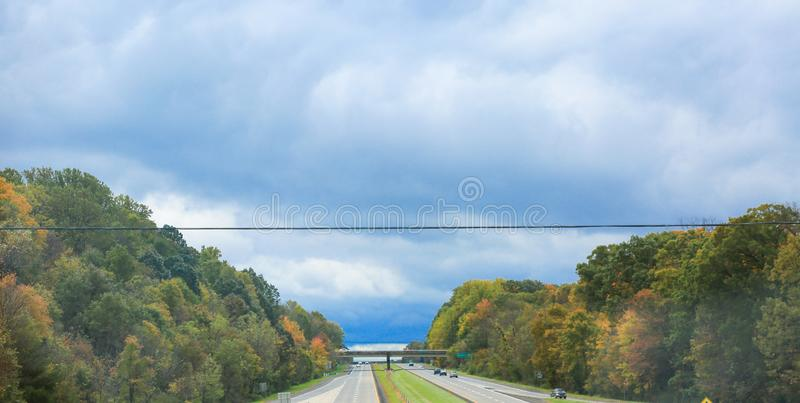 Car driving on a country road through a colorful forest at fall. Philadelphia, Pennsylvania October 28, 2018: Car driving on a country road through a colorful royalty free stock photo