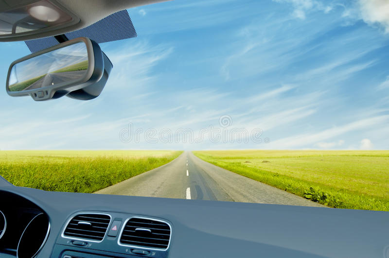 Car driving in countryside. Car driving on road through green countryside fields viewed from interior of car with dashboard in foreground royalty free stock images