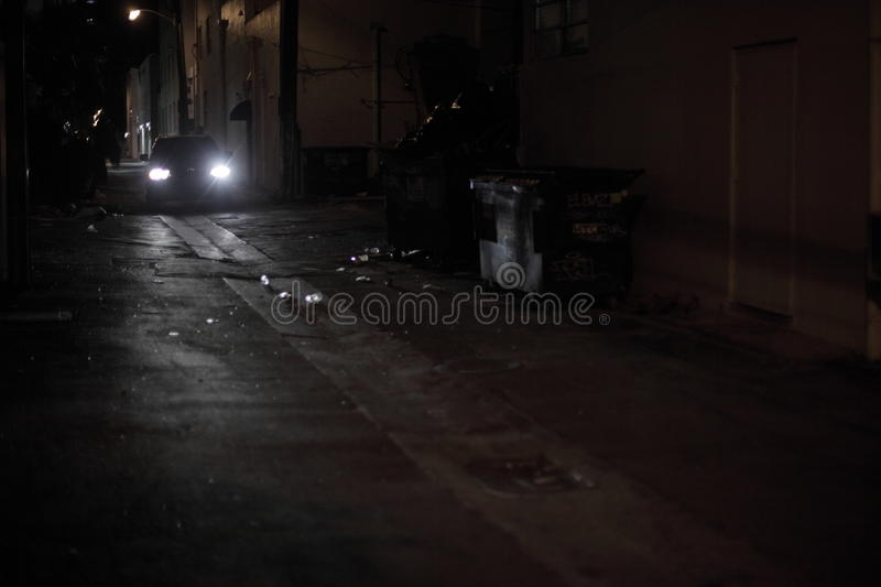 Car driving down a dark alley. At night royalty free stock image