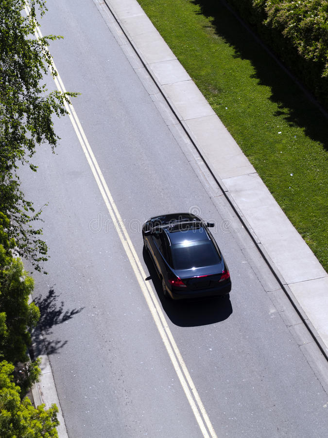 Car Driving Down Road From Above Green Grass. Lone Dark Car Shot From Above Driving royalty free stock images