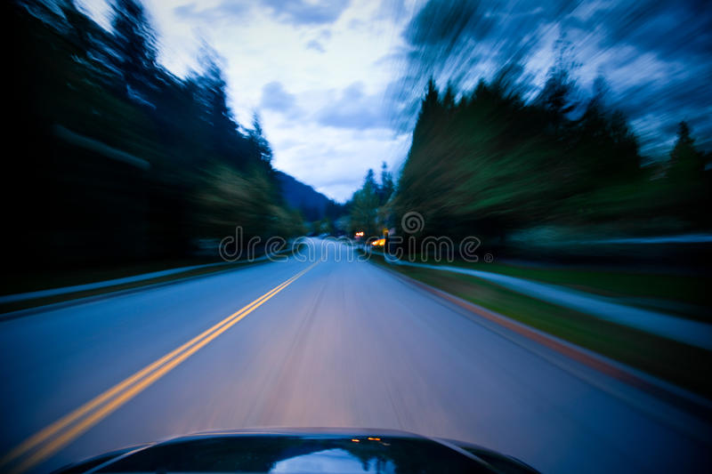Car driving fast. A car driving fast through a neighbourhood. Image shows motion blur stock images