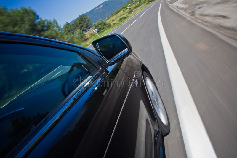 Car driving fast on a road. Car driving fast on a curvy road royalty free stock photography