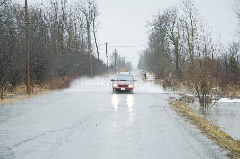 Car driving through flooded roadway royalty free stock images