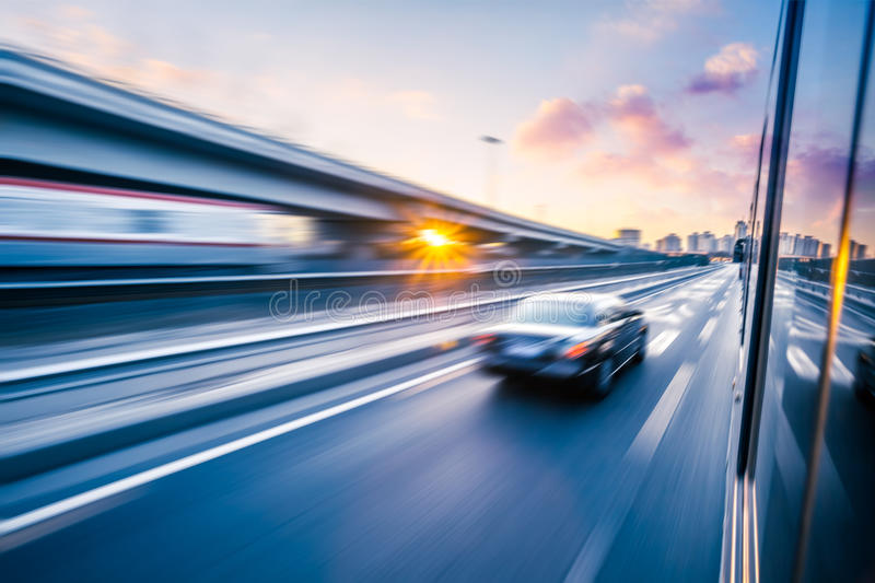 Car driving on freeway at sunset, motion blur.  stock photography