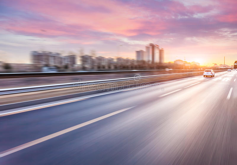 Car driving on freeway at sunset, motion blur.  stock photos