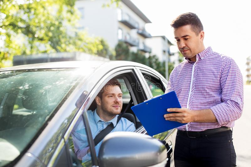Car driving instructor with clipboard and driver. Education, examination and people concept - driving school instructor with clipboard and male driver in car royalty free stock photo