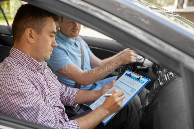 Car driving instructor with clipboard and driver. Education, examination and people concept - driving school instructor with clipboard and male driver in car stock photography