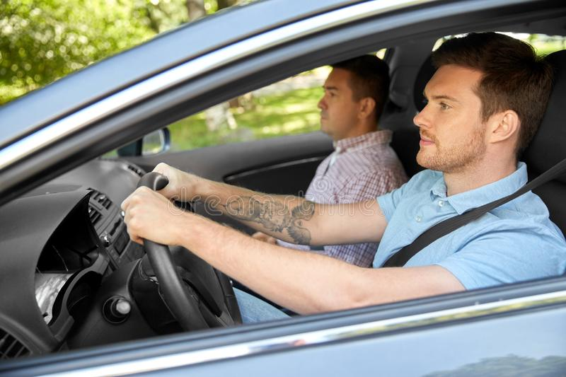 Car driving school instructor and male driver. Car driving lesson and carpooling concept - instructor on passenger seat and young driver royalty free stock photography