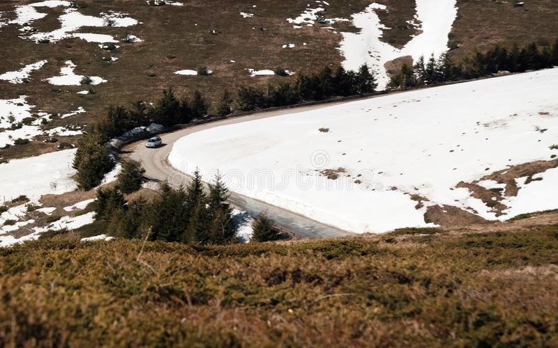 Car driving on narrow road in Beklemeto pass, Balkan mountains, Bulgaria. Melting snow in spring time, dangerous driving condition.  stock photo