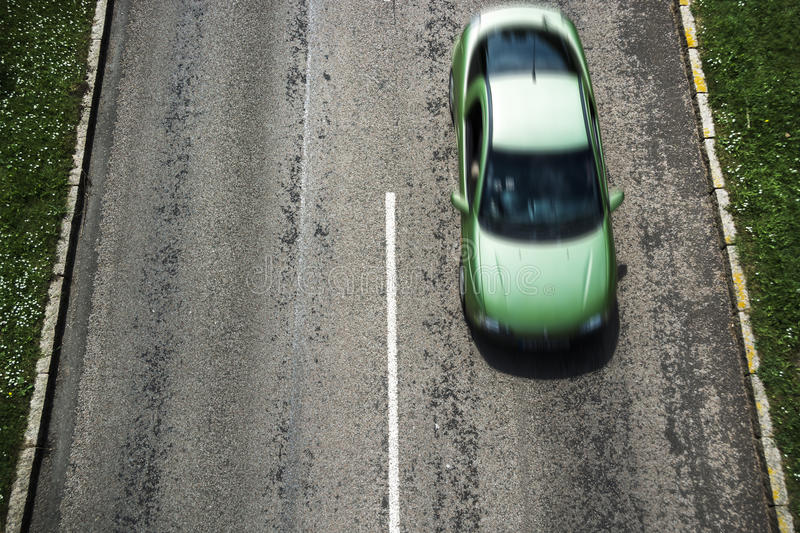 Car driving on road in green neighbourhood. A car driving on road in green neighbourhood - aerial view stock photo
