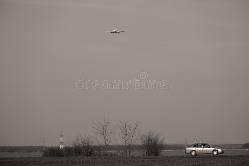 Car driving and plane flying above. Car driving on the road in the middle of a green field, plane flying above up in the sky stock image